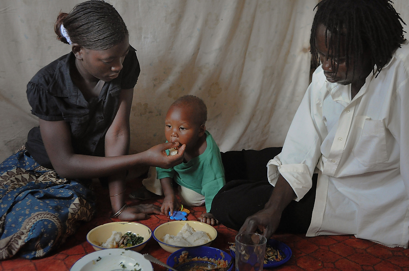 Tasila, partner Nicholas, and her son Felix eat lunch on October 4, 2010.